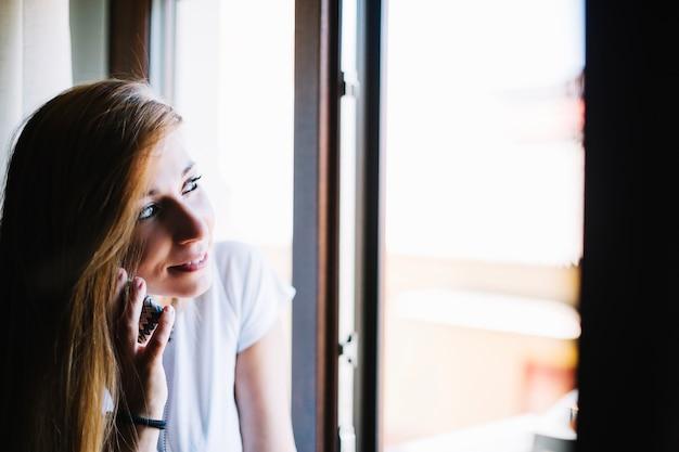 Woman talking on phone near window