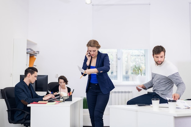 A woman talking over the phone in an open space office while walking around