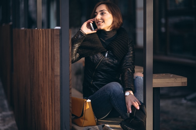 Woman talking on the phone and sitting on a bench in the street