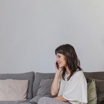 Woman talking on phone sitting on couch
