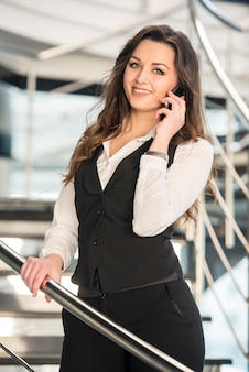 Woman talking on phone on stairs in a modern office.
