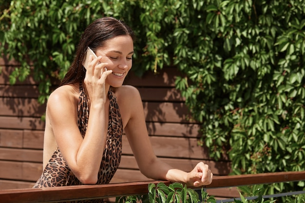 Woman talking on the phone on summer resort, posing near wooden fence with green plants