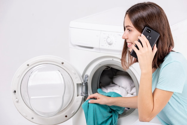 Woman talking on the phone while doing laundry