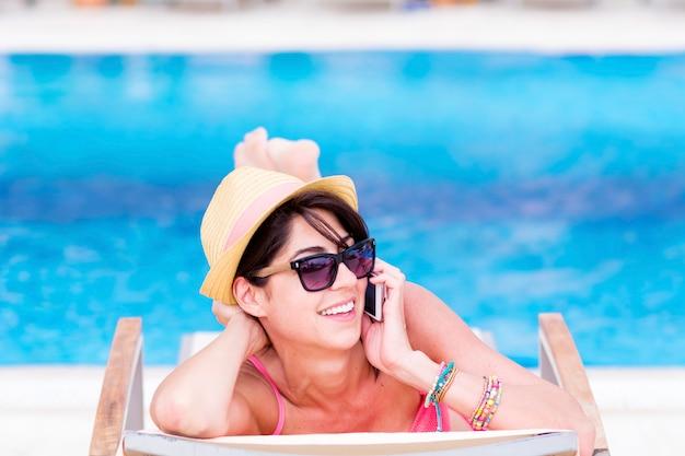 La donna parla al telefono mentre godendo una giornata di sole