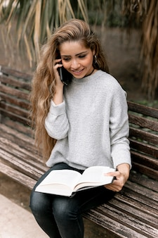 Woman talking on the phone while holding a book