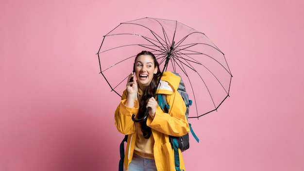 Woman talking on the phone while holding an umbrella