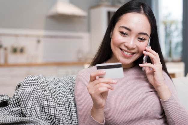 Woman talking on the phone while holding up credit card
