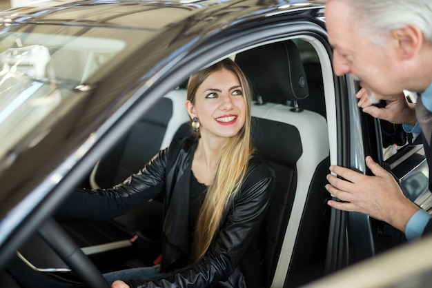 Woman talking to the salesman to buy her new car in a showroom