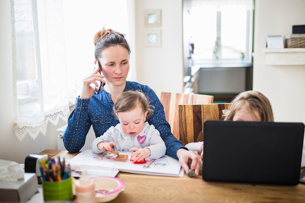 Woman talking on smartphone while her children playing over desk