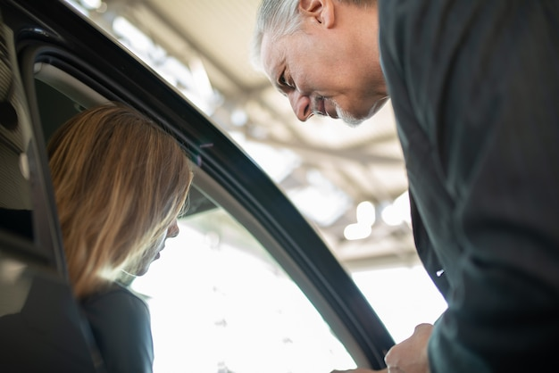쇼룸에서 새 차를 사기 위해 판매원과 이야기하는 여성