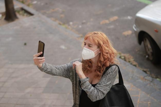 Женщина разговаривает с мобильным телефоном и медицинской маской