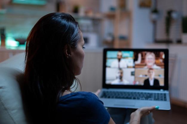 ウェブカメラでビジネスの人々と話している女性。自宅のラップトップの前でソファに横になって作業しているビデオ通話で同僚とオンライン会議、ビデオ会議コンサルティングを行っているリモートワーカー