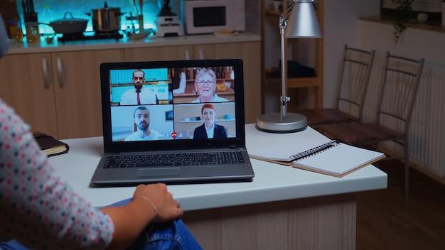 자정에 집에서 커피 한 잔을 들고 화상 회의를 하는 동안 동료들과 이야기하는 여성. 현대 기술 네트워크 무선을 사용하여 자정에 가상 회의에서 초과 근무를 하는 여성