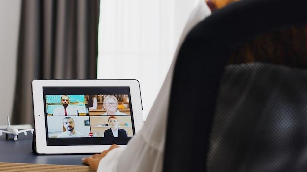 Женщина разговаривает со своими коллегами во время видеозвонка из домашнего офиса.