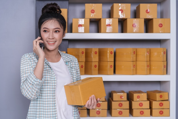 Woman talking with her smartphone at home office, small online business owner