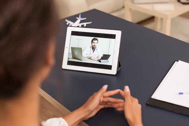 タブレットコンピューターでのビデオ通話中に医師と話している女性。
