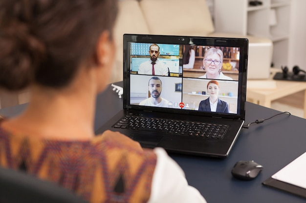 Woman talking with work colleagues on video call using tablet computer from home.