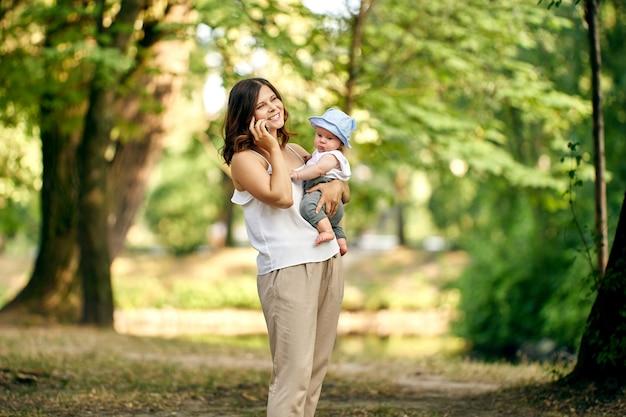 스마트폰으로 이야기하고 손에 어린 소년을 안고 있는 여성