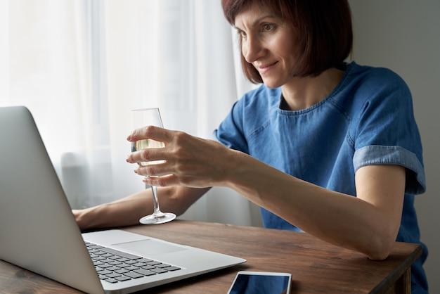 Женщина разговаривает онлайн в видеочате с друзьями и пьет вино. знакомства онлайн