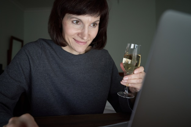 Woman talks online in video chat with friends and drinks wine.
