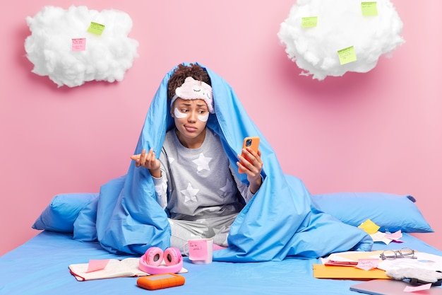 Woman talks online with friend shrugs shoulder with hesitation dressed in nightwear works from home poses on comfortable bed isolated on pink