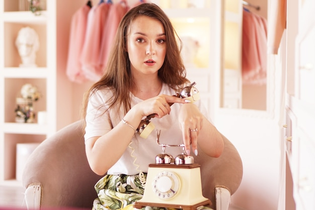 A woman talks on the phone phone handset in retro style the girl in the dressing room in pink color