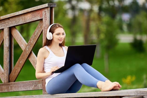 여자는 야외에서 노트북과 인터넷을 사용하여 친구들과 이야기합니다.