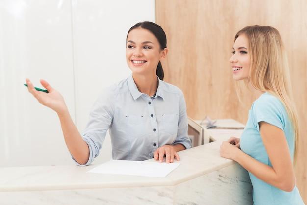 Женщина разговаривает с клиентом и показывает что-то.