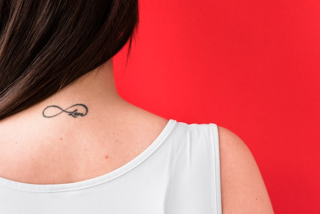 Woman in tank top with love tattoo