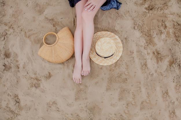 여자 그을린 다리, 밀짚 모자와 모래 해변에 가방. 해변에서 휴식을 취하고 모래 위에 발을 딛고