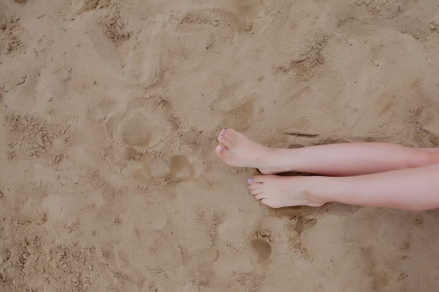 Woman tanned legs, straw hat and bag on sand beach. relaxing at a beach, with your feet on the sand.