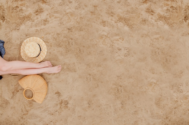 Woman tanned legs, straw hat and bag on sand beach. travel concept. relaxing at a beach, with your feet on the sand.
