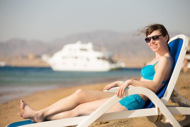 Woman tanning on blue deckchair