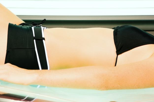 Woman tanning in solarium