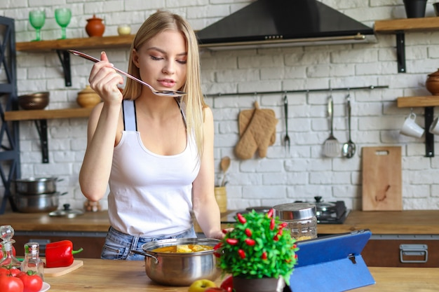 Woman tastes cooked soup, woman cooks at home