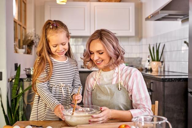 Женщина учит дочь замешивать тесто для домашнего печенья