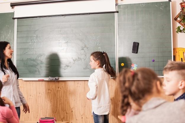 칠판에 수학 예를 해결하는 학생을 돕는 여자 교사