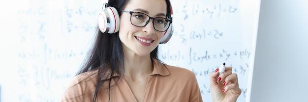 칠판 배경의 컴퓨터 화면을 보고 있는 헤드폰을 끼고 있는 여자 교사