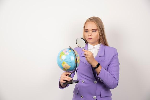 Insegnante della donna che esamina globo con lente d'ingrandimento con espressione seria.