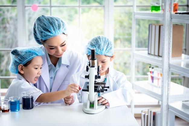 여자 교사 실험실에서 어린이 학생들을 위해 과학 실험이 수행되고 있습니다.