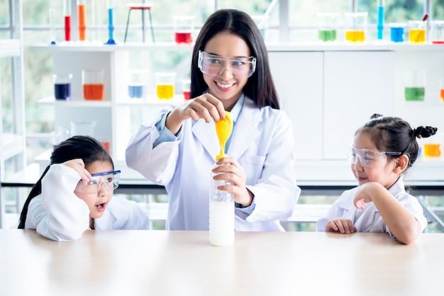 女教師風船と水筒を使って子供たちのために科学実験が行われている
