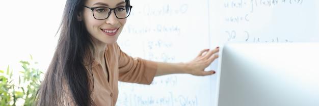Женщина-учитель стоит у доски с формулами и смотрит в экран ноутбука