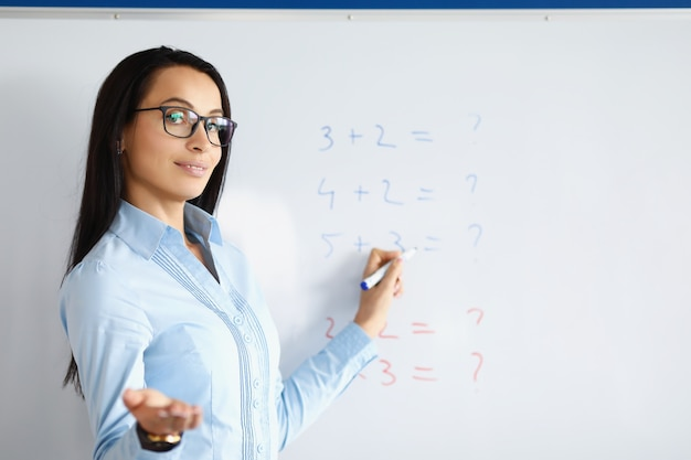Woman teacher standing at blackboard with formulas and explaining information