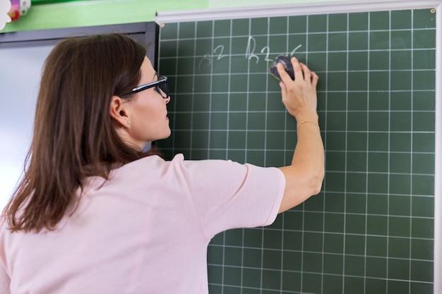 手書きのチョークテキストを拭く教室の黒板の近くに彼女の背中を持つ女教師