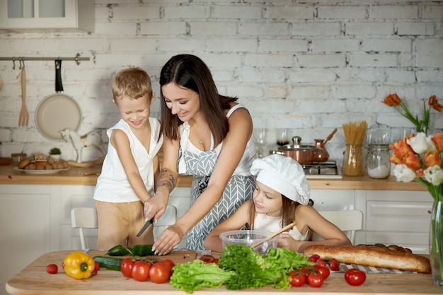 A woman teaches her daughter to cook from her son