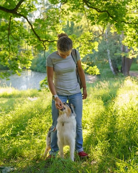 Женщина обучает очаровательную умную собаку австралийской овчарке новым командам во время тренировки на послушание