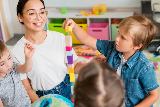 Donna che insegna ai bambini come giocare con la torre colorata