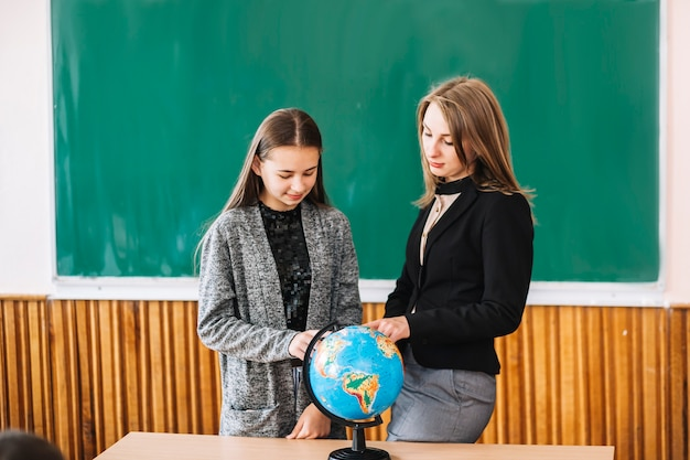 Woman teaching geography to student girl