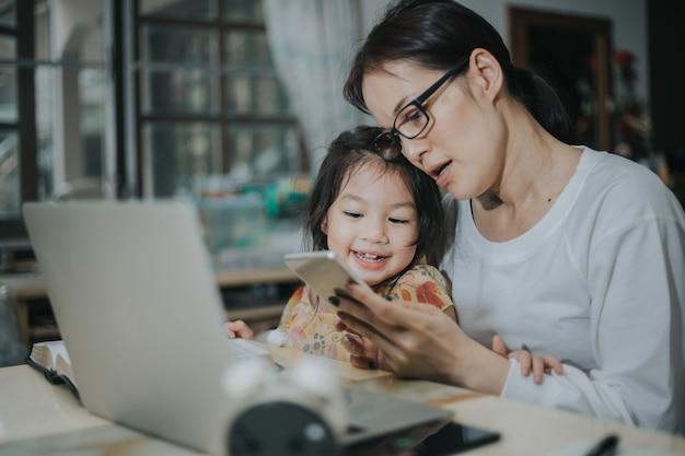 Женщина учит дочь с ноутбуком и смартфоном учиться онлайн