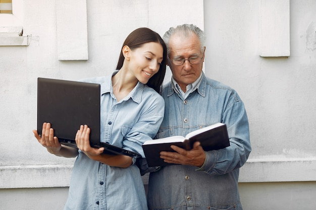 Woman teaching her grandfather how to use a laptop